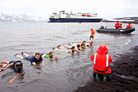 Guests from the Lindblad Expedition ship National Geographic Explorer lay in the relatively warm waters of the caldera at Deception Island, South Shet...