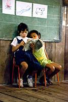 2 two young girls of indigenous Shuar Ecuadorian origin reading a book at school in a wooden building, Amazon basin, Pastaza, Ecuador