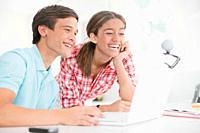 Teenage couple enjoying video chat on laptop