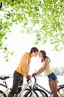 Couple on bicycles stopping and kissing