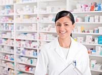 Smiling pharmacist standing in drug store