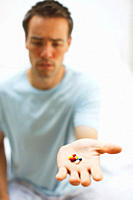 Man holding out hand full of vitamins and supplements