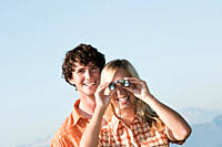Young couple standing, woman uses binoculars.