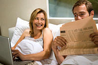 Couple in bed with laptop and newspaper