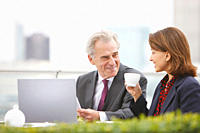 Business people drinking coffee and working outdoors