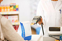 Pharmacist holding security device for customer in drug store