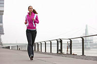 Germany, Cologne, Young woman jogging