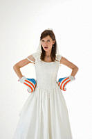 Bride wearing boxing gloves with hand on hipBride wearing boxing gloves with hand on hip