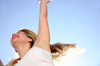 Young woman in a happy mood in front of blue sky, view from below