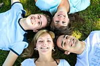 Four young people smiling up at the camera, Germany, Europe