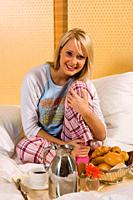 Young girl having breakfast in bed in her pajamas