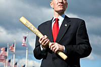 A politician holding a rolled up US Constitution