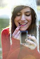 Portrait of a cute and sweet spanish teenager girl painting her lips in red