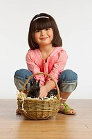 A Girl Petting A Rabbit In A Basket