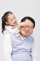 Granddaughter covering grandfather´s eyes