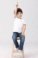 Boy sitting on stool pointing