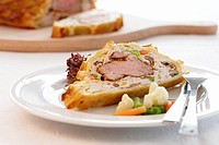 Pork fillet wrapped in puff pastry with vegetables