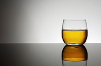 closeup of a glass of whiskey with a white background