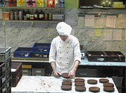 Young Chef preparing Sacher Torte Cakes in the kitchen of Cafe Demel, Vienna, Austria