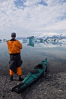 Kayaker looking at the icebergs of the Joekulsarlon glacial lake, Iceland, Europe