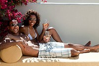 Happy couple on lounger with wine