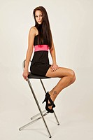 Young woman with long brown hair, black dress and high heels posing on a bar chair