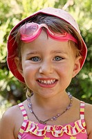 Three year old girl wearing sun hat swimming goggles and swimsuit looking straight at camera and smiling.