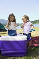 Young sisters preparing food on a cooler at a campsite.