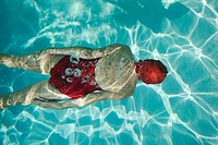 Overhead view of a woman swimming underwater.