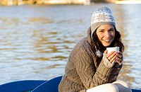 Woman holding mug in row boat