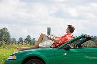 Man on car hood using laptop