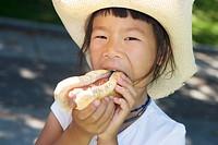 Closeup of girl eating hot dog