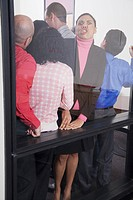 Businesswoman pushing up against glass wall