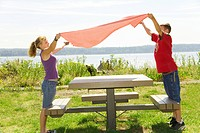 Boy and girl placing table cloth on picnic table