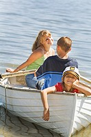 Boy and girl in row boat with young sibling