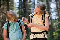 Canada, British Columbia, Fernie, two girls examining animal closed in jar
