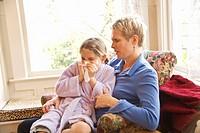 Mother watching sick daughter blow nose