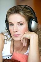 Frau liegt am Boden und hoert Musik, woman lying on the floor and listening to music