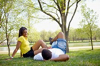 African American couple laying in grass in park