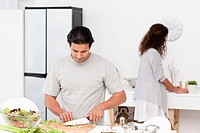 Hispanic couple preparing a salad together in the kitchen for lunch