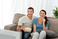 Lovely couple laughing while relaxing in front of the television at home