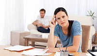 Worried woman doing her account while her boyfriend waiting in the living room at home
