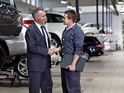 Businessman shaking hands with mechanic in auto repair shop