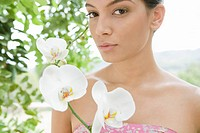 Beautiful woman holding blooming orchid