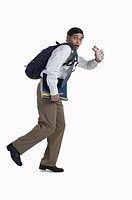 Young businessman with backpack running, portrait