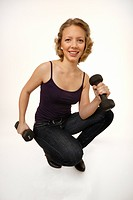 Young woman using dumbbells, squating, smiling, feeling good
