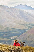 Young woman resting, enjoying panorama, view, Wind River Valley, Northern Mackenzie Mountains, Yukon Territory, Canada