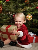 Two year old girl sitting under a Christmas tree with a gift in her hands