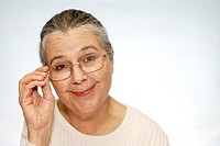 Smiling older woman touching glasses on face