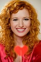 Portrait of a young woman with a heart shape lollipop.